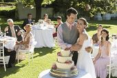 stock photo of cake stand  - Happy young bride and groom in front of wedding cake while guests sitting in garden - JPG