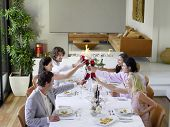 Group of multiethnic friends toasting wineglasses across table at dinner party