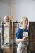 stock photo of senior class  - Two adult students painting at easels in art class - JPG