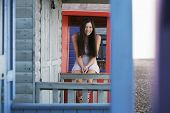 image of herne bay beach  - Portrait of happy young woman sitting on balustrade of beach house - JPG