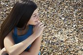 pic of herne bay beach  - Thoughtful young woman looking away while sitting at beach - JPG