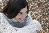 stock photo of herne bay beach  - Closeup of thoughtful young woman looking away while sitting at beach - JPG