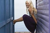 stock photo of herne bay beach  - Side view portrait of happy young woman sitting on balustrade of beach cabin - JPG