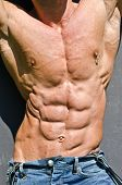 stock photo of nipple  - Bodybuilder torso with arms up ripped abs and pecs with nipple piercing wearing jeans - JPG