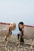 stock photo of herne bay beach  - Portrait of happy female friends sitting on deckchairs at beach - JPG