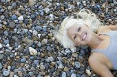 picture of herne bay beach  - High angle portrait of beautiful young woman lying on pebbles at beach - JPG