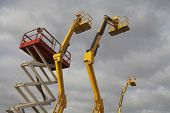 stock photo of cherry-picker  - Hydraulic lift machines against stormy sky - JPG