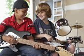stock photo of preteen  - Happy multiethnic boys playing guitars in garage - JPG