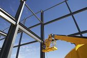 stock photo of cherry-picker  - Welder working from cherry picker on steel framing structure - JPG