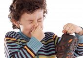 image of stinky  - Cute young boy with stinky shoe pitching his nose - JPG