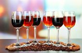 Glasses of liquors with almonds and coffee grains, on bright background