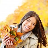 Autumn / Fall woman holding colorful leaves in city park smiling happy. Stylish modern portrait of g