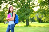 Back to school student girl looking to side in park holding books and note books wearing backpack. F