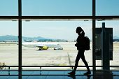 picture of leaving  - Silhouette of young woman walking at airport - JPG