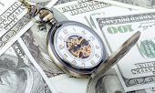 picture of watch  - Concept of time is money old watch on a pile dollar notes - JPG