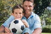 Happy dad and son with a football in a park smiling at camera