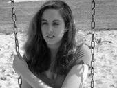 stock photo of swingset  - a black and white photograph of a young woman on a swingset - JPG