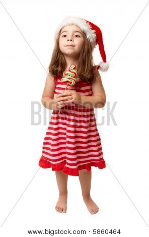 Little Girl Wearing Santa Hat And Holding Christmas Candy