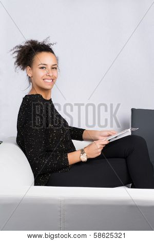 Young Woman Reads A Magazine