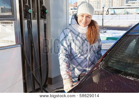 Woman In Winter Clothes Standing With Refuel Pistol Near Car