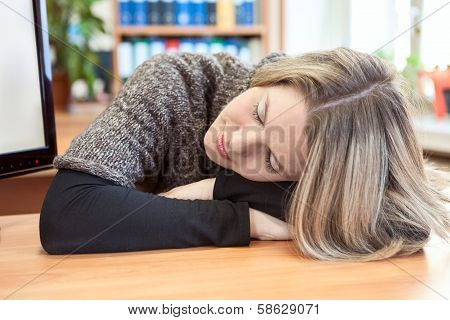Attractive Woman Sleeping On Hands At Table In Office