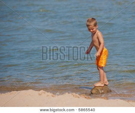 Boy Balancing On A Rock