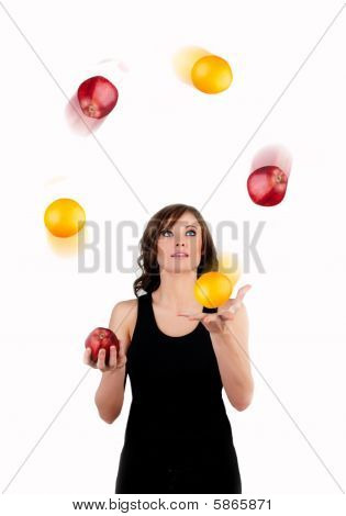 Beautiful Woman Juggling Apples And Oranges On A White Background