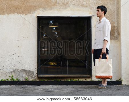 Man With Canvas Bag On Grunge Concrete Background