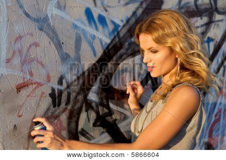 Woman Spraying Graffiti On A Wall