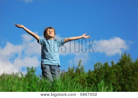 boy standing with spreading hands on the field against the sky
