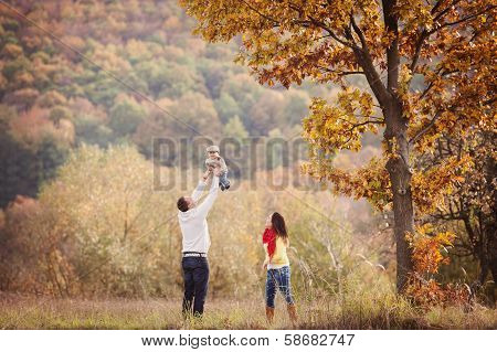 Family relaxing together in golden autumn nature