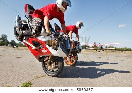 Two men doing stoppie