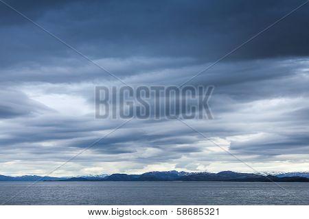Dark Blue Stormy Sky Over Coastal Rocks. Empty Norwegian Sea Landscape