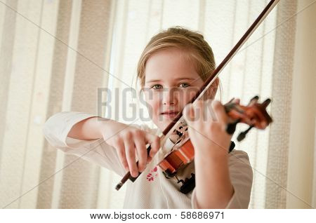 Smiling child playing violin at home