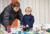 picture of exposition  - Father and little son having fun on toy exposition indoors - JPG