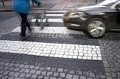 stock photo of zebra crossing  - Senior citizen crossing street with fast car approaching - JPG
