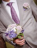picture of fiance  - closeup of a fiance in suit with wedding flowers