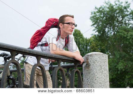 Backpacker lean on the granite embankment parapet