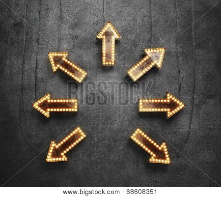 Arrows with light bulbs on a black wall