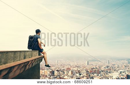 Young man is sitting on a roof and looking city