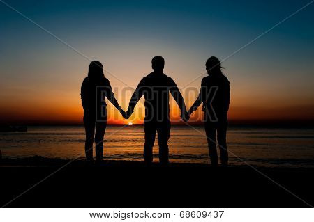 Silhouette of three friends in the morning at the beach