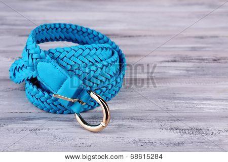 Blue leather belt on wooden background