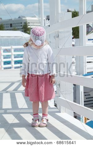 Little Cute Girl Stands On White Wooden Bridge And Looks Down