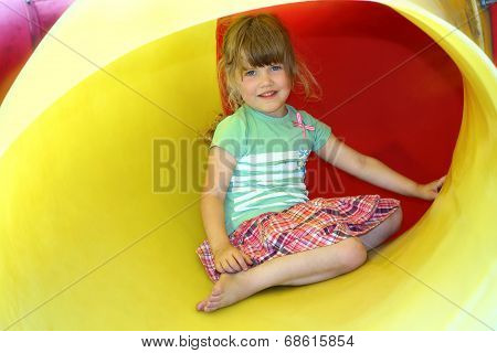 Portrait of smiling little girl inside yellow plastic tube on playground