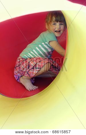 Portrait of happy little girl inside yellow plastic tube on playground