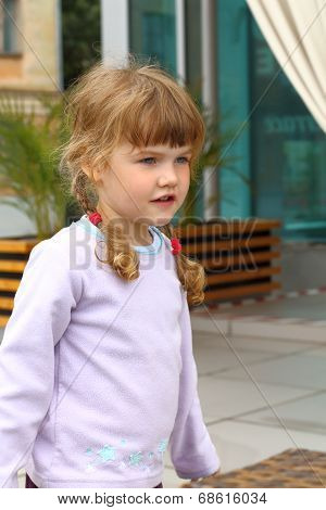 Portrait of little girl with two braids in summer cafe