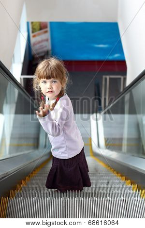 Little girl with two pigtails coming down escalator