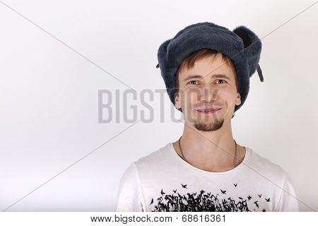Happy Handsome Young Man In Grey Cap With Earflaps Smiles In Studio