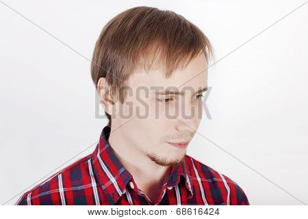 Young Man With Beard In Checkered Red Shirt Thinks And Looks Away