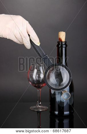 Taking fingerprints with bottle of wine isolated on black